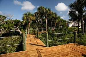 A long walk path from the home leads to a private dock.