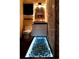 On the other side of a 25 ft stone wall is a half bathroom, which features an illuminated riverstone flooring.