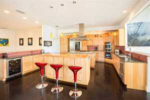 Kitchen features beautiful granite and stained concrete counter tops flanked by gorgeous custom built cabinetry. Stainless Sub-Zero & Jenn-Air appliances include 2 dishwashers, 2 refrigerators, 6 burner gas cooktop, double-ovens, multiple warming drawers and beverage cooler.