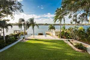 The lawn offers full potential for outdoor gatherings by the lake.