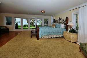 Enjoy cool, romantic evenings by opening the glass French doors to Lake Fairview from the first floor master bedroom.