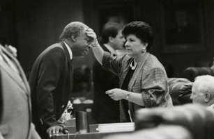 Representative Elaine Gordon checks a man's head.