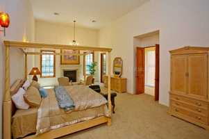 Downstairs master retreat offers a sitting area and fireplace, with French doors leading to the lanai.