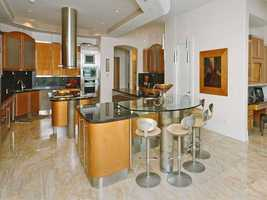 The modern kitchen features new appliances, a cooking island, marble floors and a bar that seats five.