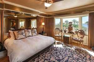 Upstairs, the large bay window in the master bedroom looks out onto the deck with and offers views of the grounds, pool and 90-feet of sandy beach spanning the lakefront.