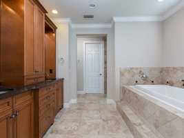 The en suite master bathroom features extravagant, customdual vanities completely separate from each other. Plus, a large elongated spa tub.