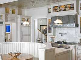 The kitchen features top of the line appliances and a tin, vaulted ceiling.
