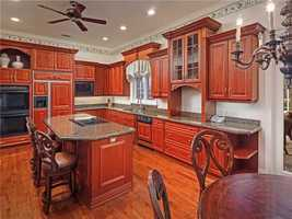 The kitchen boasts a large working island adjacent to the well-equipped butler's pantry complete with wine racks, a sink and a dishwasher.