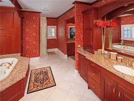 The large master bathroom features a lot of wood.