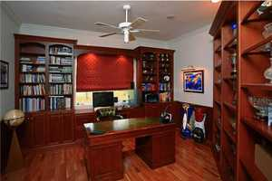 Home office features custom wood bookshelves and desk.