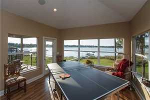 "This open floor plan encourages tranquility and socializing. So this ""sun room"" is currently also used for ping pong."