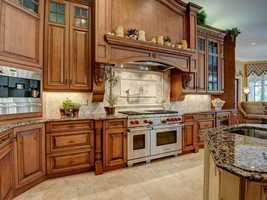 Spacious chef's kitchen with custom solid wood cabinetry, Wolfe Stainless Steel 6 Burner Range, Granite Counter Tops, Franke Triple bowl sink