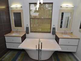 Between the dual vanities is a romantic spa tub.