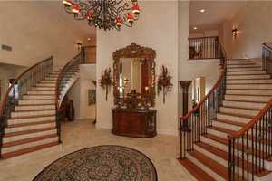 Enter the two-story foyer with \stone floors and a sweeping double staircase. The iron chandelier is originally from the historic San Juan Hotel in downtown Orlando.