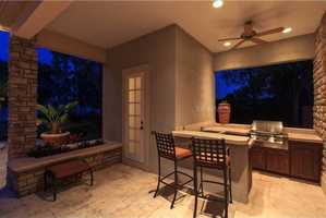 The summer kitchen features a gas grille, wet bar & beverage refrigerator, bar seating and private half bathroom.