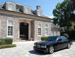 At the main house, you are greeted by a stone exterior and 12 ft. tall custom mahogany front doors.