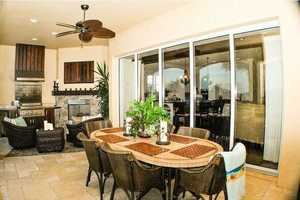 Relax in the Mediterranean style courtyard featuring a fireplace or on the travertine lanai featuring an outdoor kitchen, TV, and a second fireplace overlooking the saltwater pool