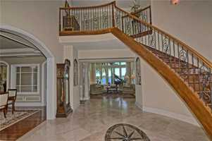 Vaulted ceiling  and marble floors great you in the foyer.