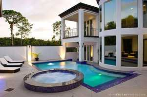 The majestic pool area boast an expansive pool, jacuzzi, and uncovered lounging space.