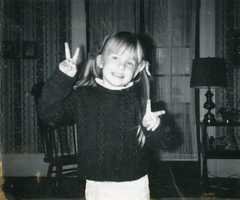 Who is this young girl flashing the peace sign?