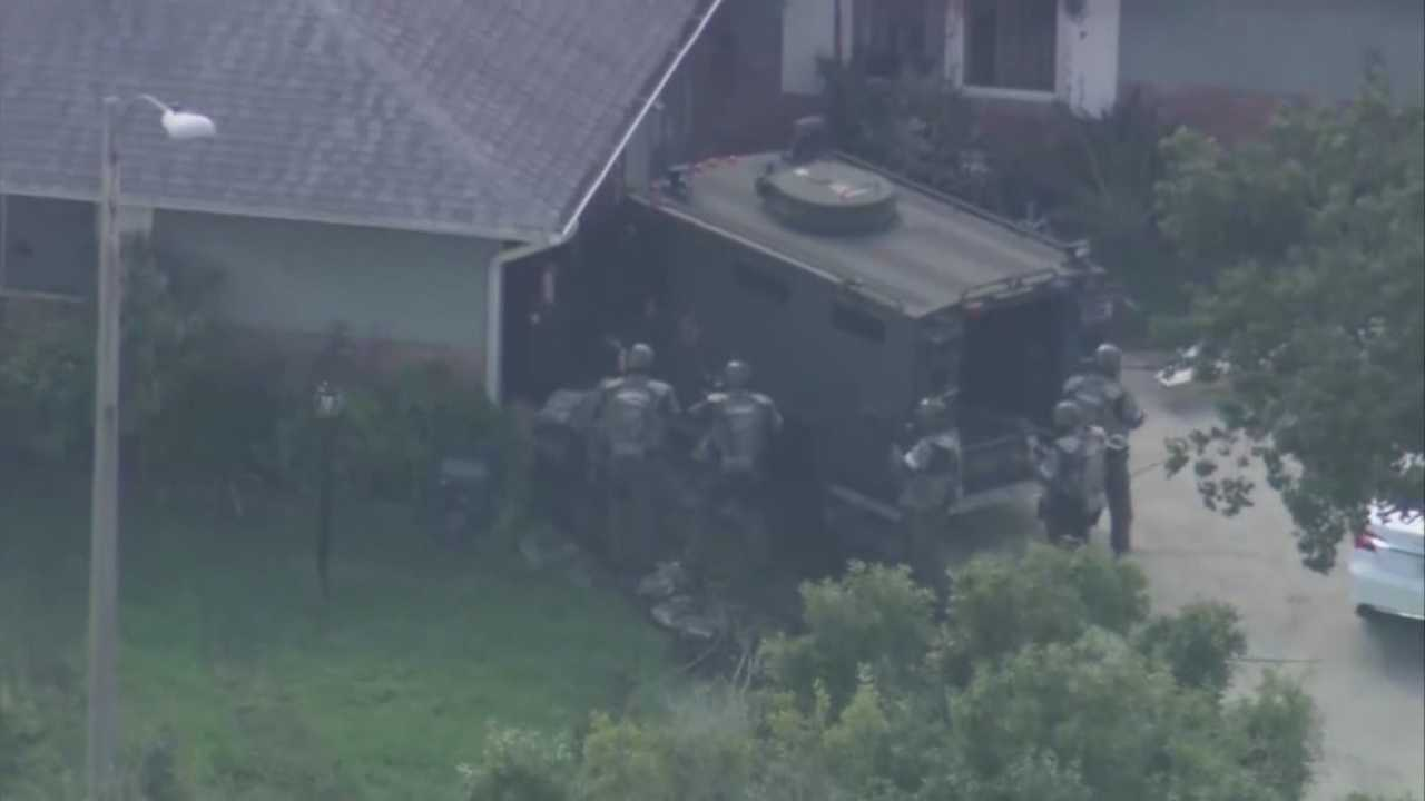 A man wanted on murder charges barricaded himself inside an east Orange County home for more than 10 hours Friday, officials said.