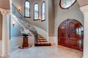 The foyer seamless blends monastery style doors and windows with modern tile floors and wall panels.