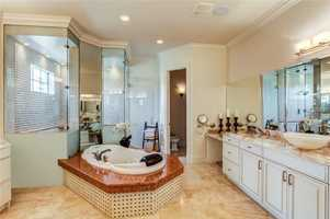 Master bathroom features double layered onyx counters with vessel sinks, jetted tub and walk in shower.