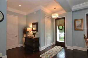 The foyer boasts hardwood floors, 10 ft. ceilings, and recessed lighting.