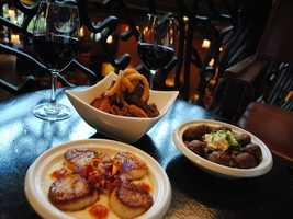 "Disney officials describe this new option as ""Peri Peri Scallops are four pan-fried scallops with mealie grits, bacon lardons, coriander and chile butter."" To the right behind the scallops are crispy chickpea bites, which Disney officials describe as ""bite-sized fritters served with sag dahl, Tunisian olive oil, lemon balm, roasted eggplant salad and sautéed feta cheese."""
