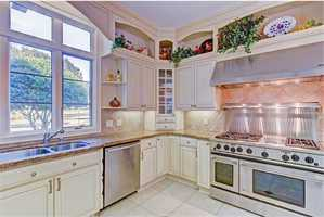 The spacious kitchen also boats with rich glazed cabinets,granite counters,GE Monogram appliances with a 6 burner gas range and walk-in pantry with counter space for large appliances.