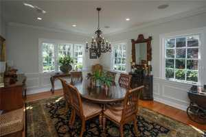 The dining room features hardwood floors, recessed lighting, and a chandelier.