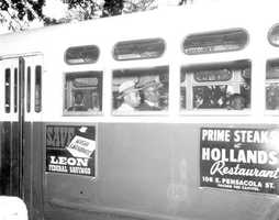 Reverend C. K. Steele (center left), and Reverend Dan Speed (center right), protesting segregated bus seating in Tallahassee by sitting in the middle instead of at the back of the bus on Dec. 24, 1956.