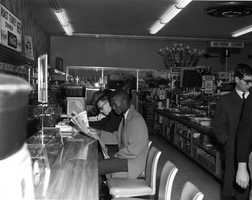 Sit-in at Woolworth's lunch counter on March 13, 1960 in Tallahassee. The white student reading at the counter is Bobby Armstrong and at the far right is reporter George Thurston.