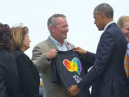"Orlando Mayor Buddy dyer shows President Obama a black ""Orlando Pride"" t shirt with a rainbow heart."