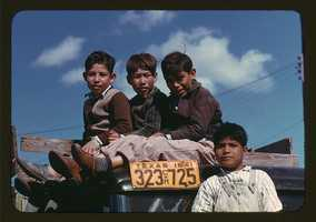 Boys sitting on truck parked at the FSA labor camp in Robston, Tex. Arthur Rothstein took this photo in January 1942.