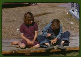 Boy building a model airplane as a girl watches at the FSA camp in Robstown, Tex. Arthur Rothstein captured this image in January 1942.