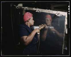 """Operating a hand drill at Vultee-Nashville, a woman is working on a """"Vengeance"""" dive bomber in Tennessee. Alfred T. Palmer took this photo in February 1943."""
