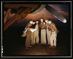 A combat crew receives final instructions just before taking off in a mighty YB-17 bomber from a bombardment squadron base at the field, Langley Field, Va. This photo was taken by Alfred T. Palmer in May 1942.
