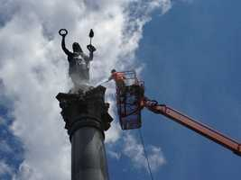 Workers are perched atop lifts to allow them to clean some of the park's biggest monuments, like this one – the New York Monument in the National Cemetery.