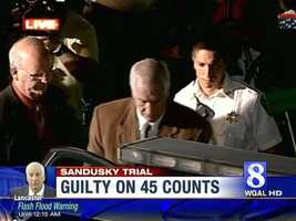 Jerry Sandusky is led to a police car before being taken to prison.