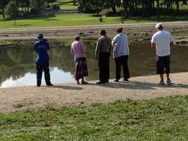 The victim's family gathers at Kiwanis Lake on Monday morning.