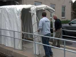 Workers set up a tent at the back entrance of the Centre County Courthouse in Bellefonte.