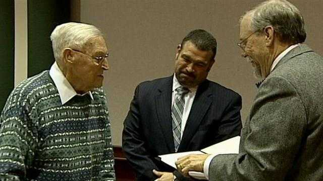 Stanley Snyder (left) receives his high school diploma.