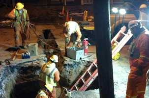 Crews work on the sinkholes Tuesday evening.