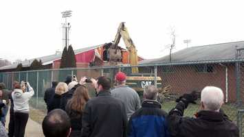 A crowd watched as a backhoe started tearing down the Biddle Field locker rooms at Dickinson College Thursday morning to make way for a new athletic building.