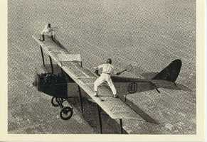 """As time went on, the acts became more and more brazen. This photo shows stunt men Ivan Unger and Gladys Roy """"playing tennis"""" on a moving airplane."""
