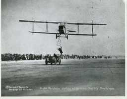 Here, stunt manClyde Pangborn leaps from a moving car toward a ladder dangling from a plane. The photo was taken in 1920.