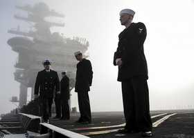 Sailors aboard the aircraft carrier USS Nimitz (CVN 68) prepare to man the rails as the ship gets underway in Everett, Wash.