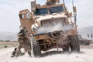 46. A U.S. Army paratrooper with the 82nd Airborne Division's 1st Brigade Combat Team fires his M4 carbine at insurgents during a firefight June 30, 2012, Ghazni Province, Afghanistan. The vehicle he is using for cover is a Mine Resistant Ambush Protected vehicle.