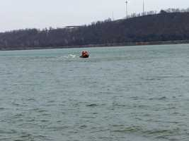 Crews tow an empty, damaged boat to shore on the Susquehanna River.